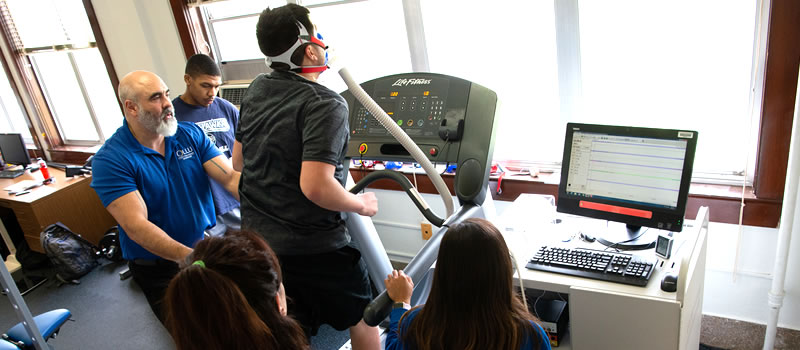 Professor works with students in kinesiology lab
