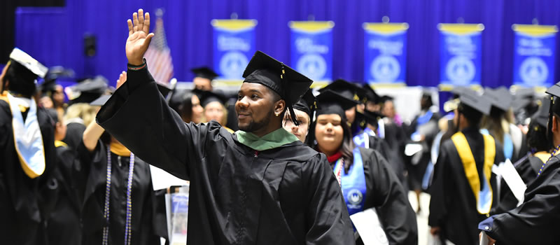 Male graduate smiling waving hello