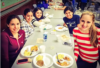 Group of female students having breakfast smiling