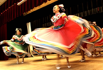 Female folklorico dancers performing on stage