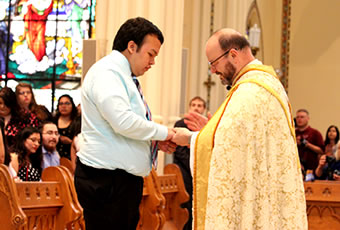 Male student receiving ring blessing in chapel