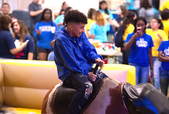 Male student riding mechanical bull