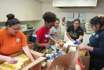 Group of students fill boxes of food at the food bank