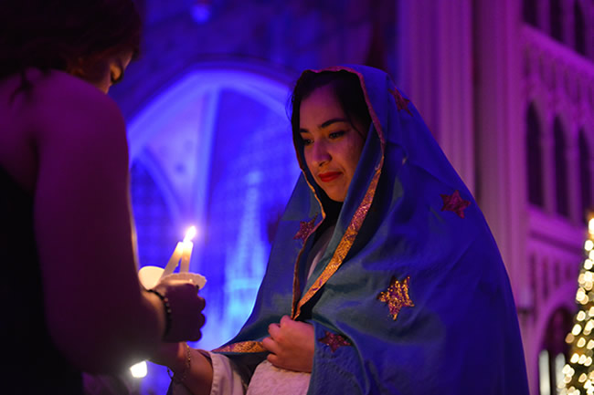 Female student dressed as Mary lighting candle