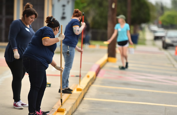 Female voluteers painting parking curb