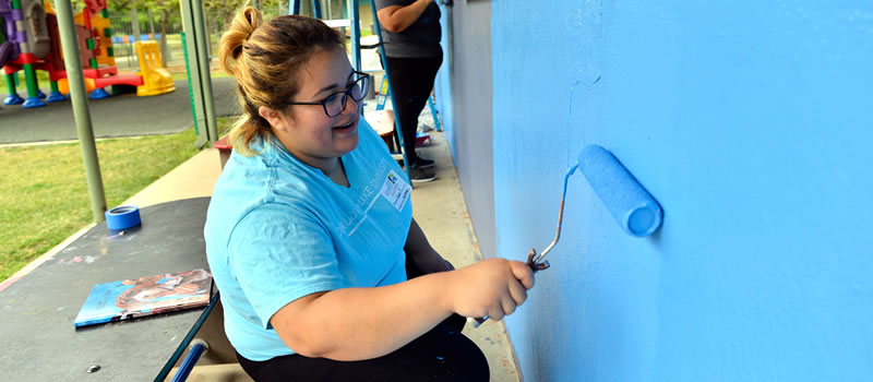 Female volunteer painting wall