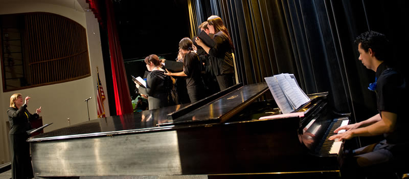 Music professor directing students on stage