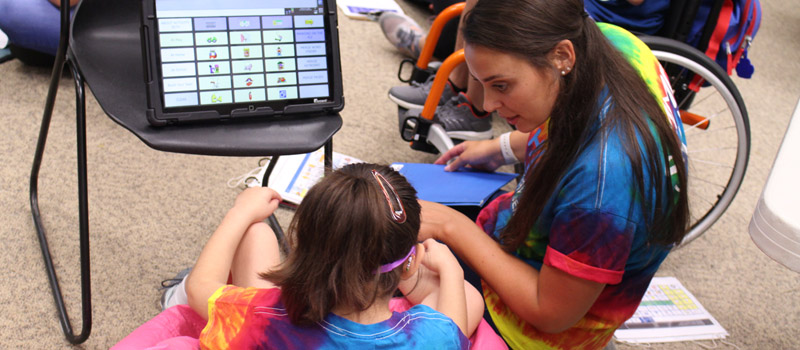 Female child using aac device during Jersig Center summer camp