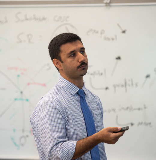 Professor standing in front of white board
