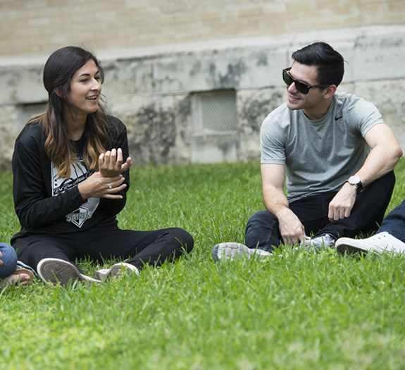 Male and Female sitting on grass talking
