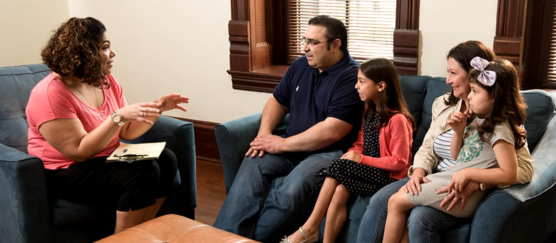 Family sitting on couch during session with social worker